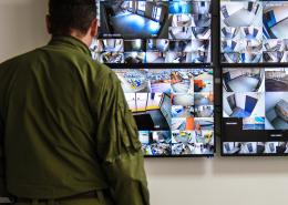 Ladendetektiv steht vor den Überwachungsbildschirmen