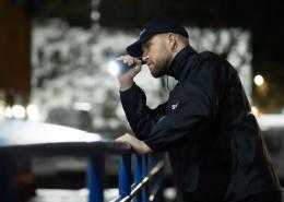 Sicherheitsmitarbeiter mit Taschenlampe nach der Security Ausbildung